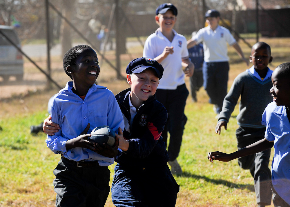 An impromptu game of rugby breaks out between children from Ebony Park Primary School and St. Stithians College Prep Tuesday, June 8, 2010 during a Dreamfields Project event in the Ivory Park township of Johannesburg, South Africa. The Dreamfields Project is a non-profit organization that aims to put resources for playing soccer into townships and rural areas in South Africa. Students from St. Stithians raised money to buy complete soccer uniforms for Ebony Park and another township team. Photo by Bahram Mark Sobhani