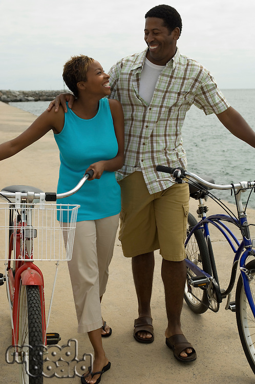 Couple walking with bicycles on beach