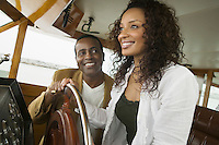 Couple at steering wheel on yacht