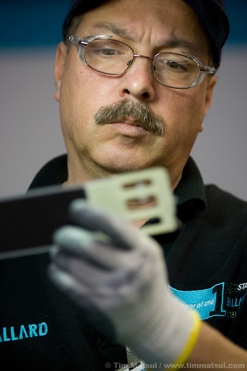 Paraschiv Stancu, with Ballard Power Systems, inspects a membrane electrode assembly (MEA), the critical component of a fuel cell, at the Ballard production plant in Vancouver, British Columbia, on March 2, 2006.  An MEA, made up of two electrodes (carbon fiber sheets coated with two thin layers of platinum-based catalyst) separated by a polymer electrolyte membrane, is inserted between two carbon-based plates to form a single fuel cell (not shown).  As Ballard Power Systems develops its fuel cell technology, it is building manufacturing processes and statistical controls to enable high volume manufacturing..Ballard is testing a Ford Focus FCV as part of the five-vehicle, three-year Vancouver Fuel Cell Vehicle Program, a demonstration (the only one of its kind in Canada) that will test the vehicles in real world conditions around Vancouver and Victoria in British Columbia. Partners in the program are Ford Motor Company / Ford of Canada, the Government of Canada, the Government of British Columbia, and Fuel Cells Canada...Ballard Power Systems (headquartered in Burnaby, British Columbia) powers the Ford Focus FCV fleet with its Mark 902 fuel cell technology.  Today, Ballard fuel cells power more than 130 fuel cell vehicles on roads around the world, including 100 DaimlerChrysler cars, trucks and buses...For automotive fuel cells to be commercially viable, they must demonstrate certain performance attributes, and be cost competitive with today?s internal combustion engines.  These attributes were determine by the US Department of Energy. Ballard is focused on increasing volumetric power density (the ability to make a smaller fuel cell stack with more power output), strengthening freeze start capability, increasing durability (or lifetime) of the fuel cells, and reducing costs.  Ballard has a road map in place to demonstrate commercially viable technology with a 5,000 hour lifetime, freeze-start capability to -30 degrees Celsius, volumetric power density of 2,500 Watts