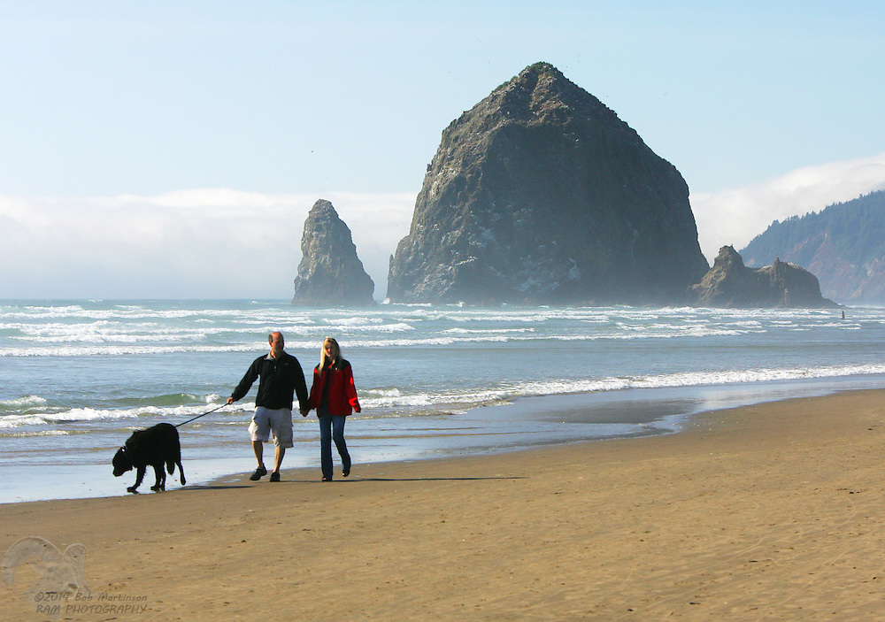 A couple walks their dog along the beach at Cannon Beach, Oregon near Haystack Rock. The area is a popular vacation getaway.