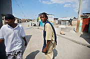 2Double, 21, walks through Cite Soleil with friend Sayid Louis, 27, on July 19, 2008. By focusing on his musical interests he has been able to steer clear of the gang activity that is endemic to the poverty-stricken area.