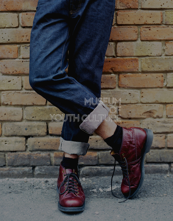 Close view of man's legs and burgundy lace-up shoes.