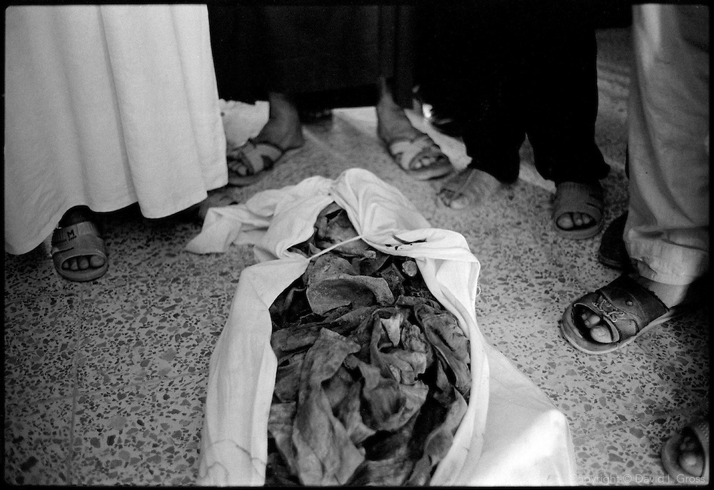A group of men stand around a body in a shroud in the  gymnasium of the local sports center in Al-Musayab, Iraq, now the home of an Iraqi human rights organization which is overseeing the exhumations of bodies from local mass graves. People come from all over to check the clothing and ID cards of the bodies, looking for relatives.