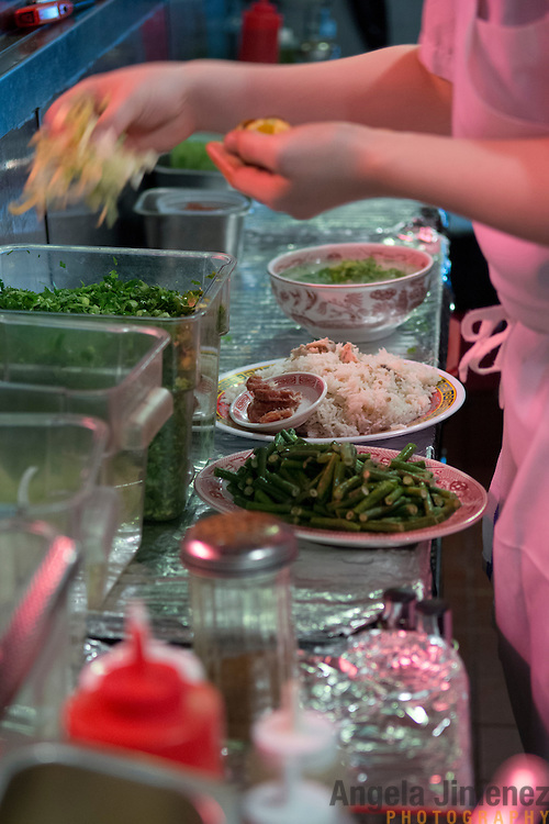 Chef Danny Bowien's restaurant, Mission Chinese, is photographed at its New York City location on the Lower East Side of Manhattan on Tuesday, July 31, 2012 in New York, NY. Here, a worker's hands are busy finishing a dish in the kitchen. .