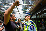 Protester Tepora Stephens (Ngati Koata, Ngati Te Wehi, Te Rarawa, Tainui, Ngā Puhi) confronts the police cordon outside the Sky City Convention centre during the<br />