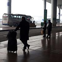 BEIJING, 15.1.2013 : Passagiere im Ankunftsbereich am Pekinger Flughafen mit ausgewaschenem Himmel im Hintergrund. In den letzten Tagen musste viele Fluege wegen Smog gestrichen werden .