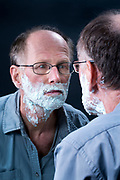 adult man looking at himself in the mirror when getting ready for shaving