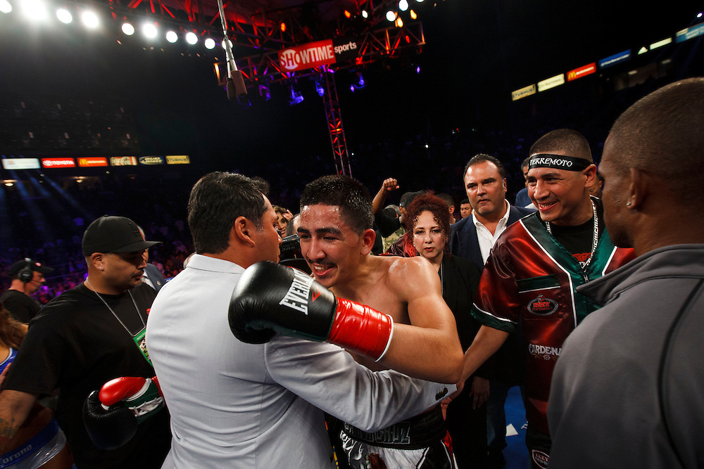 Oscar De La Hoya, as promoter of the fight, hugs Leo Santa Cruz after he knocked out Victor Terrazas for the WBC Super Bantamweight Title Fight at the StubHub Center on Saturday, August 24, 2013 in Carson, California. Patrick T. Fallon/For The New York Times