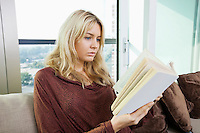 Relaxed young woman reading book in living room at home