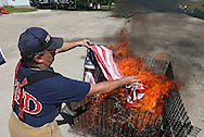 Springille Firefighter Patrick Hoyt throws a flag on the fire at the Springville Fire Department in Springville on Saturday, June 9, 2012. The flag disposal ceremony was organized by the Springville American Legion Post. (Stephen Mally/Freelance)