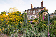 A rose covered arch in front of the house at the Laskett Gardens, Much Birch, Herefordshire, UK