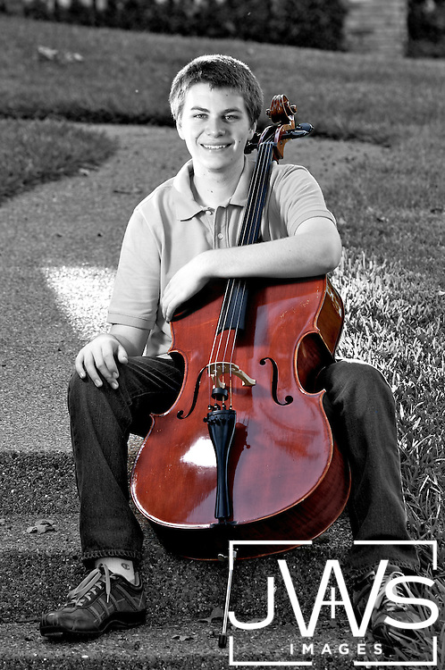 Young music enthusiast is posing with his instrument for his senior picture.