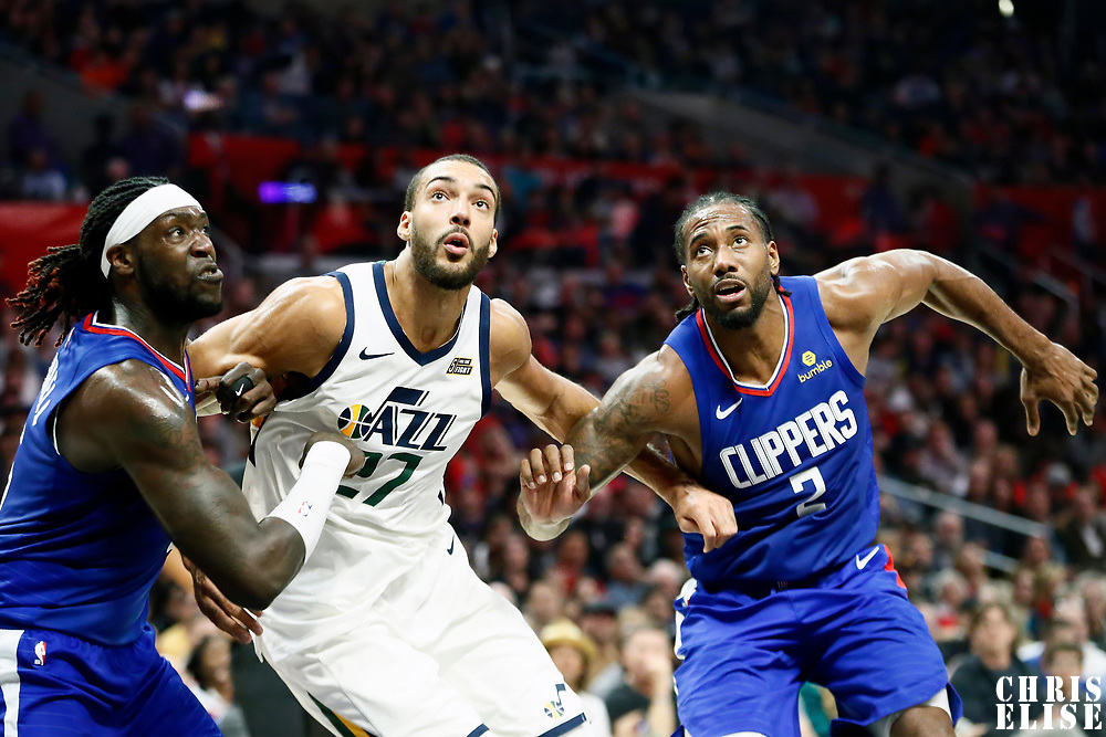 LOS ANGELES, CA - NOV 3: Rudy Gobert (27) of the Utah Jazz fights for position with Kawhi Leonard (2) of the LA Clippers and Montrezl Harrell (5) of the LA Clippers during a game on November 3, 2019 at the Staples Center, in Los Angeles, California.