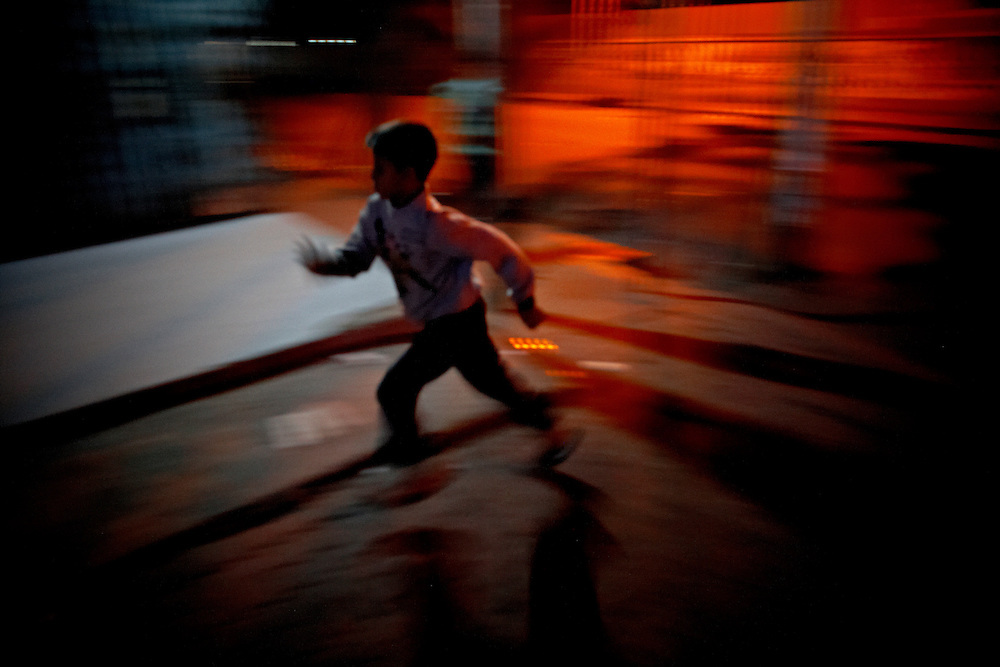 Boy running in Dhaka, Bangladesh...A boy is chasing through the streets of Dhaka...Bangladesh has finished with two years of emergency rule. The election results is compared to the landslide of 1970 that led to war and independence from Pakistan. .When preparations for the election started in late 2006, violent street-protests started, and led to a military backed interim government until the election happened under heavy security and watchful eyes on December 29th 2008...The past two years have seen a decrease of crime and corruption but also sparked violent student protests and curfews. Today  most people seem to be happy to return to some sort of normality. But in one of the poorest countries in the world where 80% live for less than a dollar a day, does it really matter who is in power? The circus is over, back to reality and putting food on the table...A blogger  from dhaka is quoted Ó we prefer messy democracy to military ruleÓ...Is this the end of night, a new dawn or yet another dusk?..Photo by: Eivind H. Natvig/MOMENT *** Local Caption ***