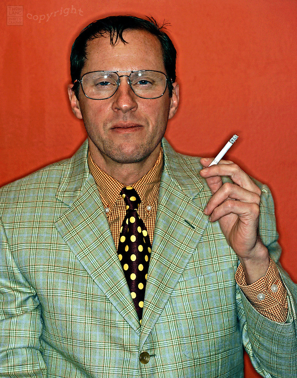 A greasy looking guy in a clashing suit holds a cigarette and squints.