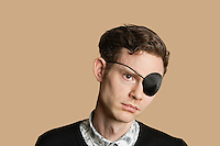 Sad mid adult man wearing eye patch over colored background