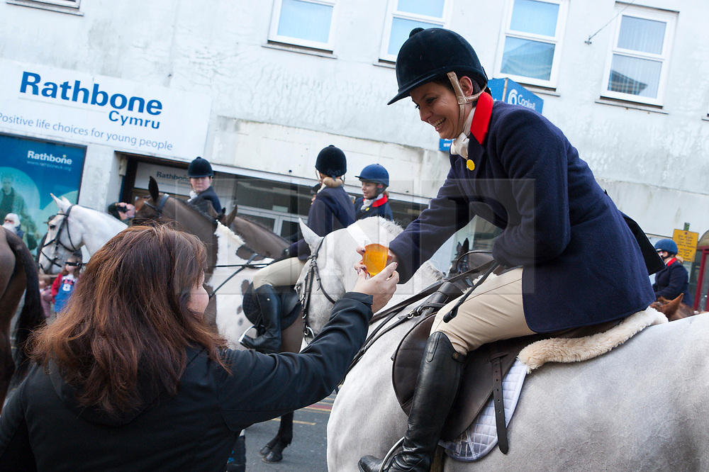 © Licensed to London News Pictures. 01/01/2019. Carmarthen, Carmarthenshire, Wales, UK. A 'Secret recipe' punch is offered to the hunt riders. The Hunt arrive in the cente of town. Anti-Bloodsport activists gather in the Welsh town of Carmarthen to voice their anger at the continued illegal hunting with dogs - hunting with dogs was made illegal in 2004 by The Hunting Act 2004 (c37). The Anti-Hunt protest takes place on the day that the Carmarthenshire Hunt have chosen to parade through the town to collect money and support for their blood-sports. Photo credit: Graham M. Lawrence/LNP