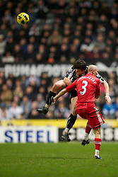 NEWCASTLE, ENGLAND - Saturday, December 11, 2010: Liverpool's Paul Konchesky is taken out by Newcastle United's Joey Barton during the Premiership match at St James' Park. (Photo by: David Rawcliffe/Propaganda)