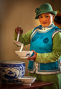 Woman serves airag, camel's milk, festival of one thousand camels, Bulgan, Gobi desert in winter, Mongolia