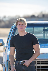 Handsome All American man leaning against a truck