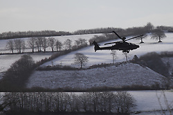 © Licensed to London News Pictures. 14/01/2015. Wheddon Cross, Devon, UK. An Apache military helicopter  performing low-level manoeuvres near Wheddon Cross near Exmoor National Park in Devon this morning, 14th January 2015. Snow has fallen overnight across many parts of England, causing travel disruption in some areas.  Photo credit : Rob Arnold/LNP