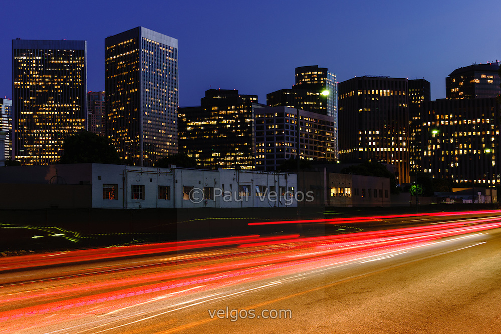 Photo of Century City California skyline buildings at night and motion blurred car lights. Image was taken in 2012 from Beverly Hills in Los Angeles County in Southern California.