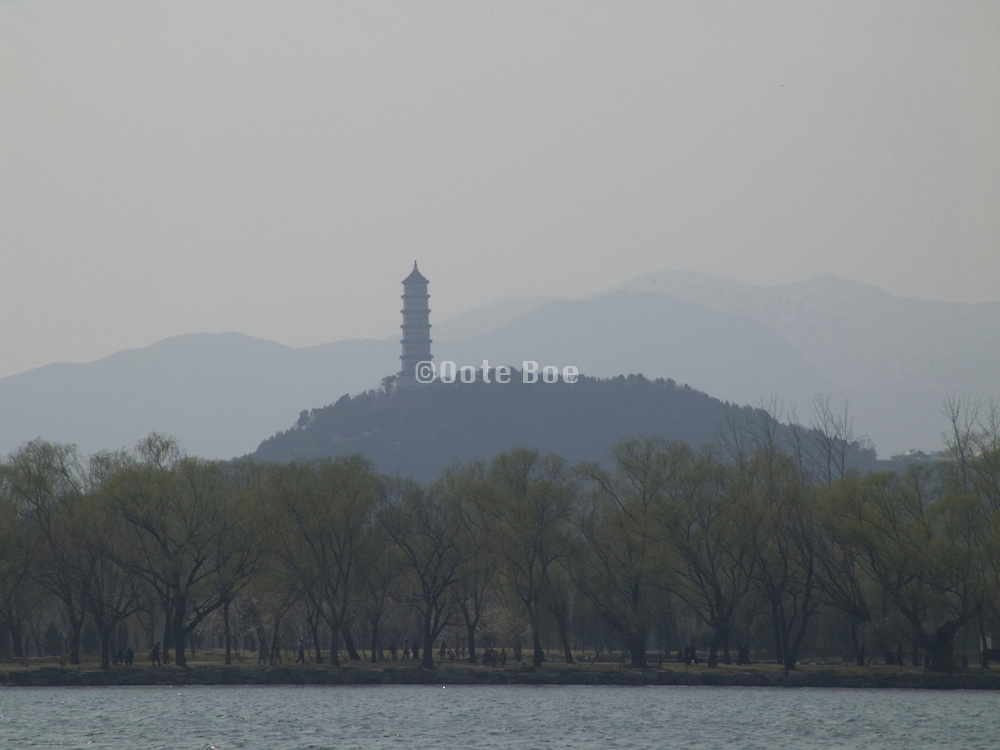 view over the lake at the Summer palace with a tower pavilion and mountains in the distance