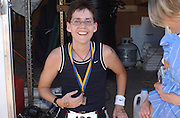 Deb Mosley finishes her triathalon at Lake Berryessa and displays her race medal for finishing. Mosley's time was 2 hours 3 minutes for the half-mile swim, 15-mile bike and 4-mile run...Photo by Jason Doiy.10-9-04.027-2004.