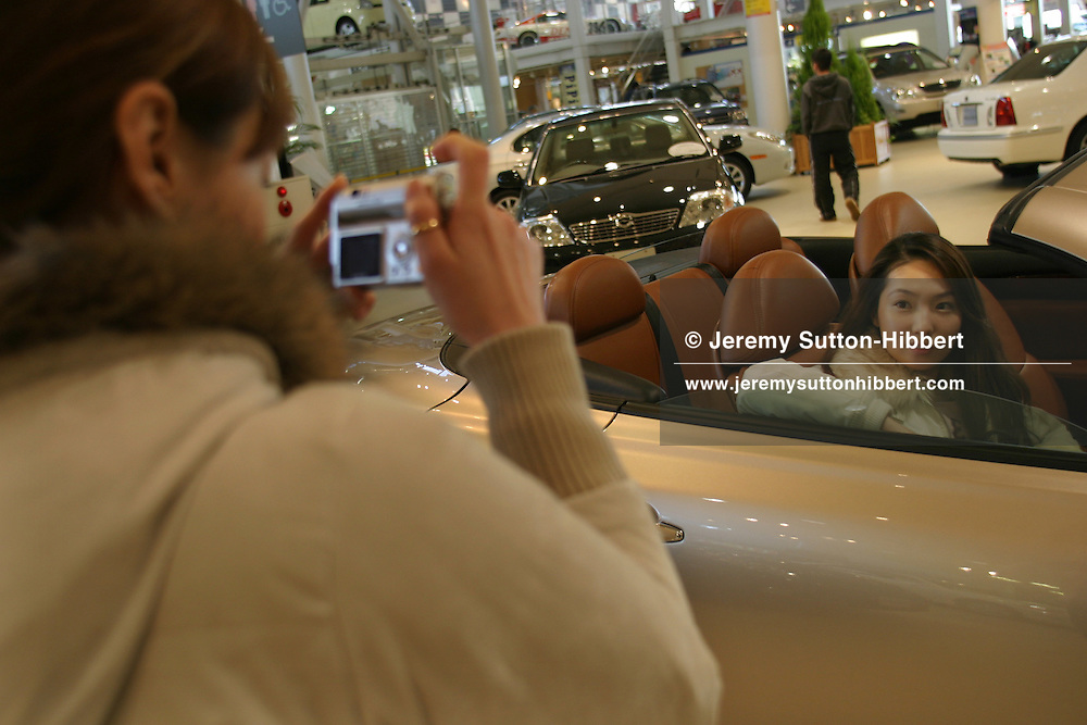 Korean girls taking photographs of each other within a Toyota car on display inside Toyota Megaweb, Tokyo, Japan.