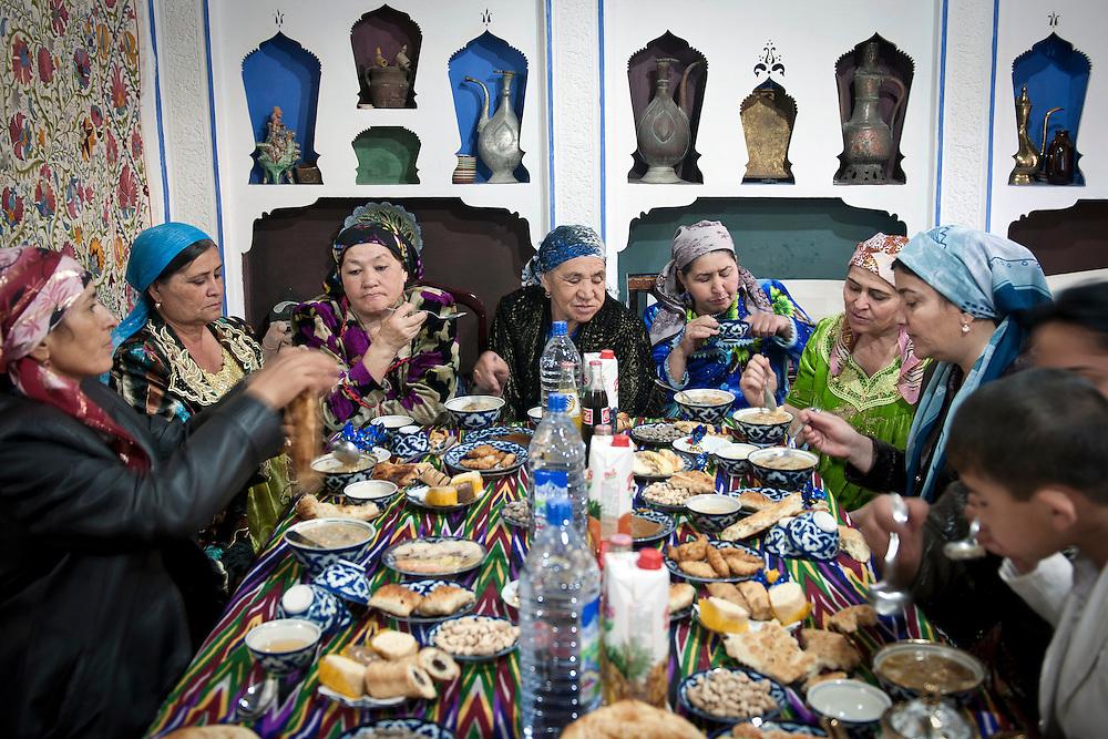 Bukhara, Uzbekistan 23 March 2012<br /> Uzbek women eat Halissa, a traditional meal during Nowruz festivities.<br /> PHOTO: EZEQUIEL SCAGNETTI