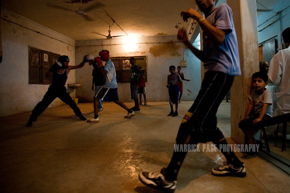 KARACHI, PAKISTAN - OCTOBER 12: Members of the Young Baloch Boxing Club train while others spar, Sunday, October 12, 2008, in Karachi, Pakistan. Lyari is Karachi's poorest, most dangerous, drug and crime-infested slum, but has produced the bulk of Pakistan's champion boxers. Boxing has been a way of survival for many of the young men, who are often sponsored by corporations and event the military, to box for them at events throughout the city and the country. Lacking in the most basic resources, including a sufficient diet, the young boxers have watched countless champions on television throughout the years, attempting to emulate their abilities. (Photo by Warrick Page)