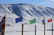 International flags fly at Green Dog Svalbard sled dog kennel in April near Longyearbyen, Svalbard, Norway.