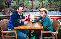 A man and woman sitting at an outdoor patio table along the Chewuch river in Winthrop, Washington at The Old Schoolhouse Brewery, USA.