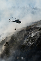 © Licensed to London News Pictures. 29/06/2018. Rheidol Valley, UK. A helicopter dumps water over a forest fire that started on Tuesday  26the June  is still burning and smouldering for a fourth day along the steep hillsides of the Rheidol Valley, a few miles inland of Aberystwyth in Mid Wales. Photo credit: Keith Morris/LNP