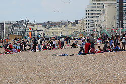© Licensed to London News Pictures. 08/07/2014. Brighton, UK. Students on a visit to Brighton having lunch on the beach.Despite temperatures in the next weeks are expected to soar to 86F around the UK with the South Coast predicted to hit record according to the MET the weather is very much cloudy today July 9th. Photo credit : Hugo Michiels/LNP