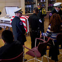 Family and colleagues gather around the casket of McKinley County Sheriffs officer Christopher Tsosie during a memorial service Wednesday at Rehoboth High School in Gallup.