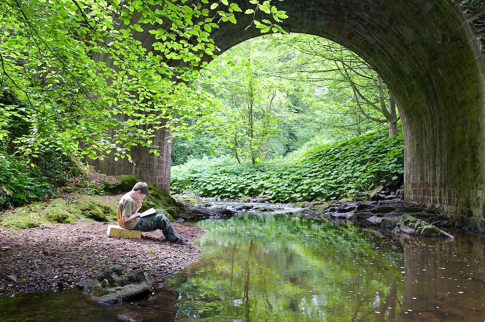 Boy reading  beside a small river, Angus, Scotland