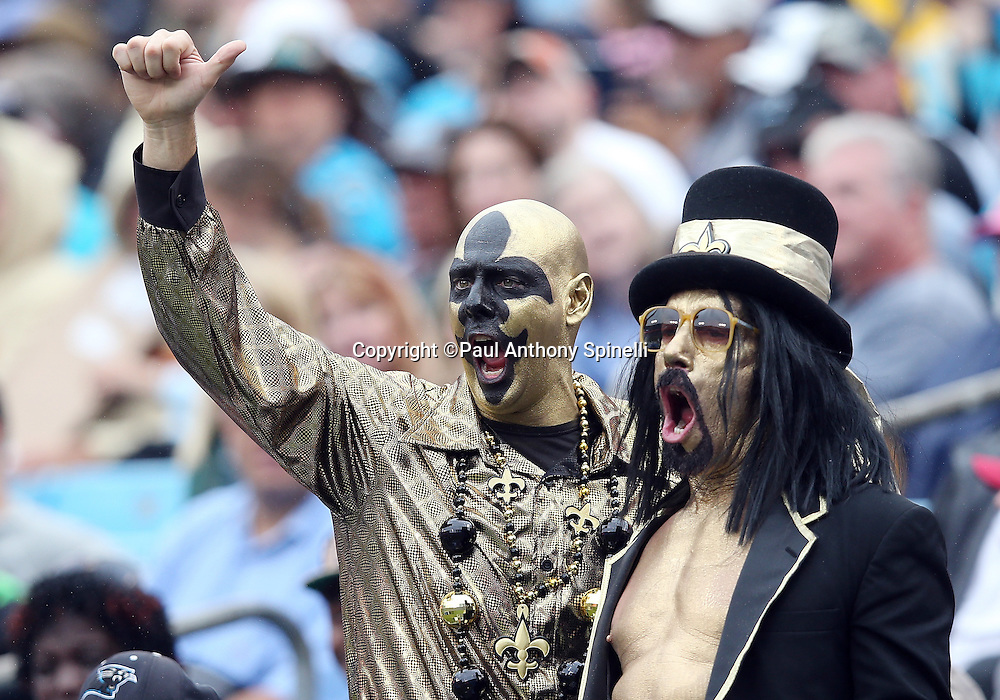 A pair of New Orleans Saints fans wearing gold and black body paint and clothes cheer for the team during the New Orleans Saints 2015 NFL week 3 regular season football game against the Carolina Panthers on Sunday, Sept. 27, 2015 in Charlotte, N.C. The Panthers won the game 27-22. (©Paul Anthony Spinelli)