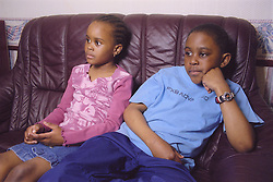 Young boy and girl sitting together on sofa watching television,
