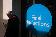Circular Final Reductions sign outside a City of London shop and coincidental round bald-headed man.