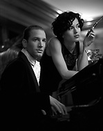 Fashion editorial - Young couple at the piano drinking martinis and smoking cigars for magazine photo shoot in Seattle, CA