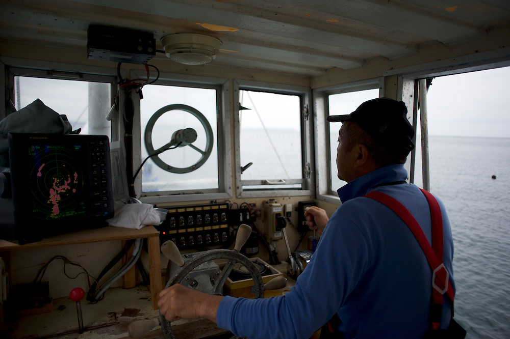 Tokuji Abe, a fisherman from Togura, pilots a fishing vessel during an early morning trip to recover nets at sea near the small village of Minami Sanriku in Miyagi prefecture. Mr. Abe, who lost his house and had his father killed during the tsunami that stroke the northeastern coast of Japan in 2011, owned a boat and worked independently before the tsunami. Due to a shortage of fishing boats in the small fishing community, Mr. Abe donated his boat to a local cooperative where the few remaining boats spared by the tsunami are shared by all.