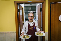 NAPLES, ITALY - 20 MARCH 2018: Giosuè, a waiter at the Pizzeria e Trattoria Vigliena, serves two dishes of spaghetti with clams in Naples, Italy, on March 20th 2018.<br /> <br /> Pizzeria e Trattoria Vigliena is a restaurant outside of the city center and adjacent to the port. At lunch, the place is packed with workers from the docks and ship owners and workers from the recently built Marina Vigliena.<br /> <br /> The restaurant is owned by Raffaele Esposito, Concetta's son and the third generation of a family of chefs who founded this restaurant in the middle of the 20th century