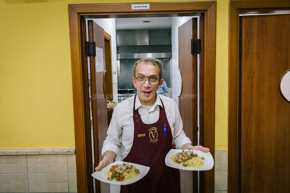 NAPLES, ITALY - 20 MARCH 2018: Giosu&egrave;, a waiter at the Pizzeria e Trattoria Vigliena, serves two dishes of spaghetti with clams in Naples, Italy, on March 20th 2018.<br /> <br /> Pizzeria e Trattoria Vigliena is a restaurant outside of the city center and adjacent to the port. At lunch, the place is packed with workers from the docks and ship owners and workers from the recently built Marina Vigliena.<br /> <br /> The restaurant is owned by Raffaele Esposito, Concetta&rsquo;s son and the third generation of a family of chefs who founded this restaurant in the middle of the 20th century