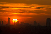 UNITED KINGDOM, London: 19 April 2018 The sun rises behind the chimneys of Battersea Power Station and a London skyline this morning on what will be yet another warm day. Londoners will be enjoying the weather again today as high temperatures are set to continue in the capital. Rick Findler / Story