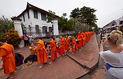 Laos. Luang Prabang. Tourists watching the early morning alms round of the Buddhist monks.