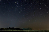 Campbell Hall, New York - Stars shine in the night sky above a farm field on Dec. 14, 2012. The photograph was taken during the Geminid meteor shower. A faint meteor is visiable high above the hay wagon on the left side of the frame. The yellow light above the horizon at right is light pollution. ©Tom Bushey / The Image Works