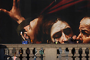 Visitors in front of the National Gallery's construction hoarding featuring their current exhibition about Caravaggio, on 17th January 2017, in Trafalgar Square, London England.
