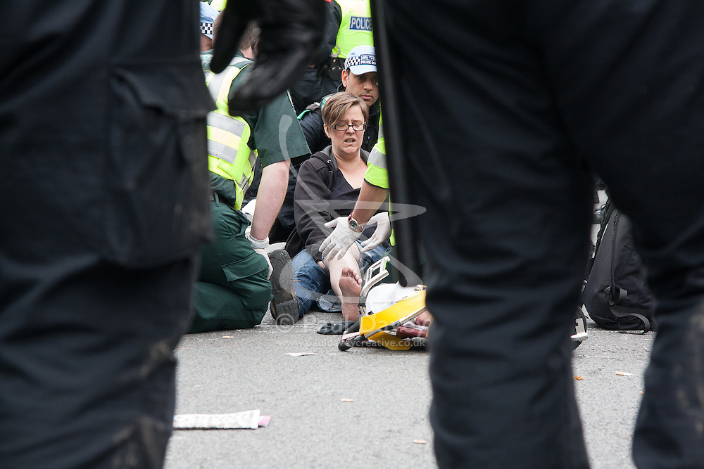 """London, February 11th 2015 Teacher Amy Jowett is treated by paramedics after suffering a broken leg on June 1st 2013 during a protest against the BNP who were attempting to march through Westminster to the Cenotaph. She claims she was """"seriously and deliberately assaulted by a police officer who repeatedly stamped on her leg during the protest, suffering """"life-changing injuries"""" requiring seven operations as well as therapy to deal with the psychological impact."""
